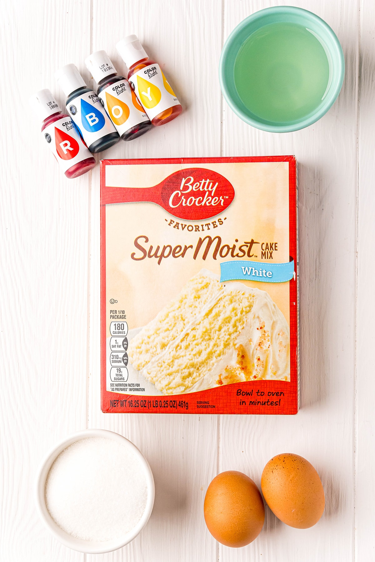 The ingredients needed to make cake mix cookies, a box of white cake mix, vegetable oil, eggs, granulated sugar, and food coloring.