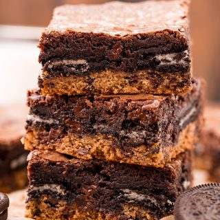 A stack of three slutty brownies with a layer of cookie, Oreo, and brownie on top.