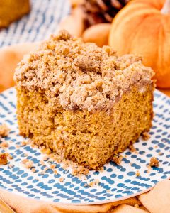 A piece of pumpkin coffee cake with a brown sugar streusel crumb topping on top.