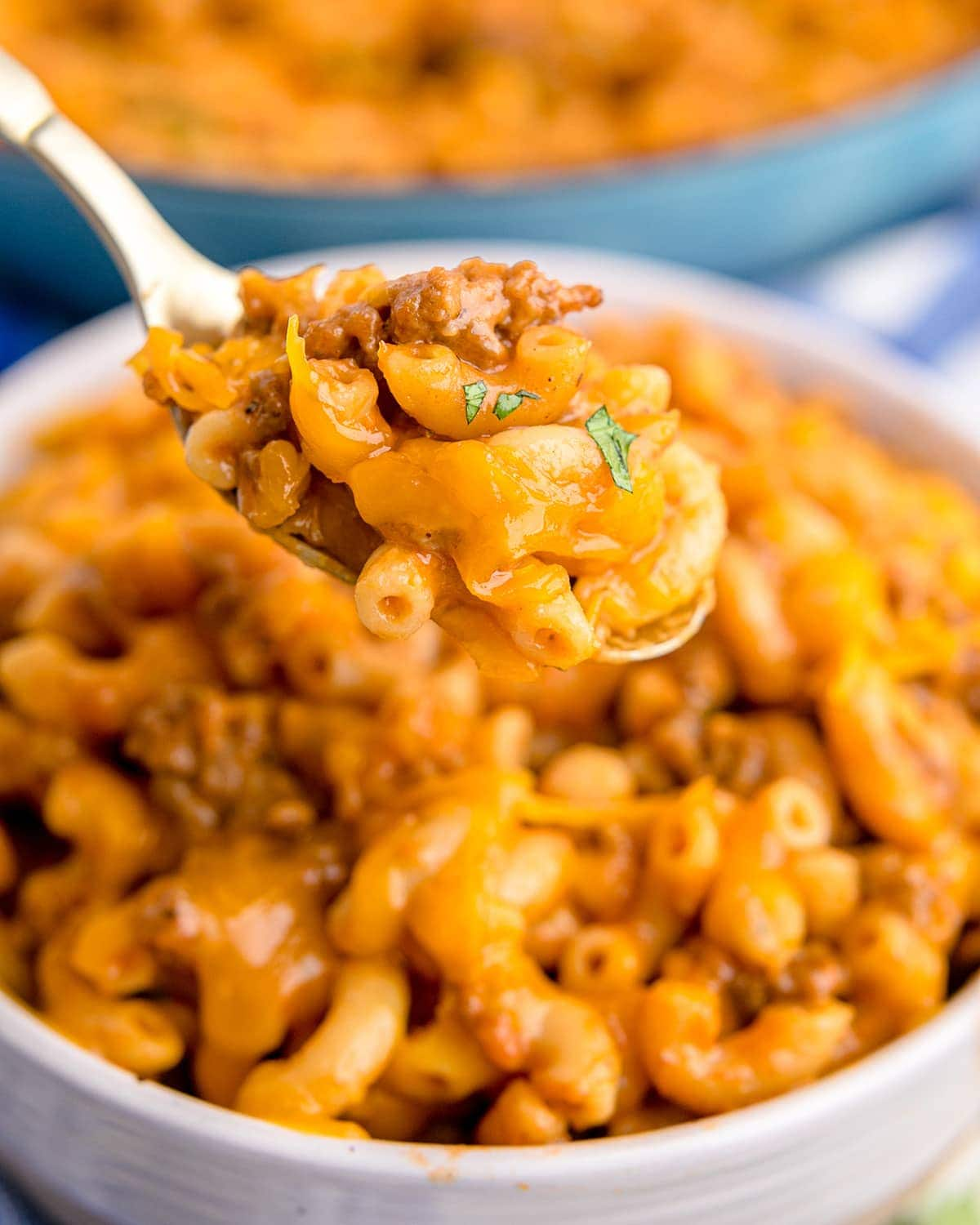 A spoonful of homemade hamburger helper being held above a bowl.