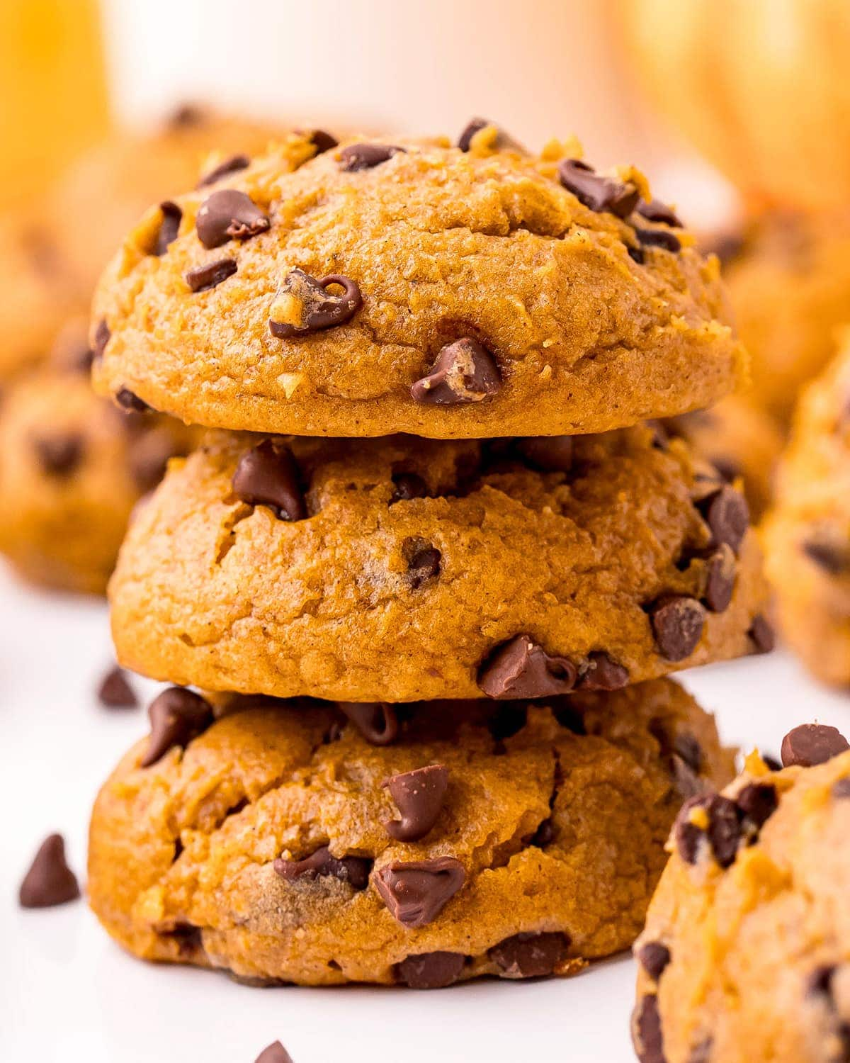 A close up of a stack of pumpkin chocolate chip cookies.