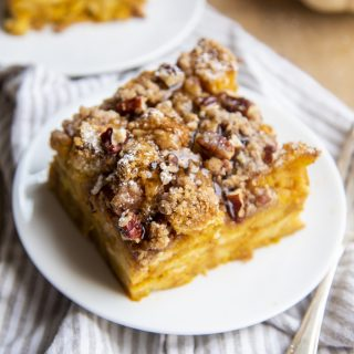 A piece of pumpkin French toast casserole on a white plate, topped with syrup.