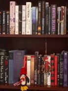 A penguin and buffalo-riding Santa make a temporary home of the bookshelf.