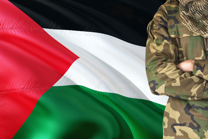 Crossed arms Palestinian soldier with national waving flag on background