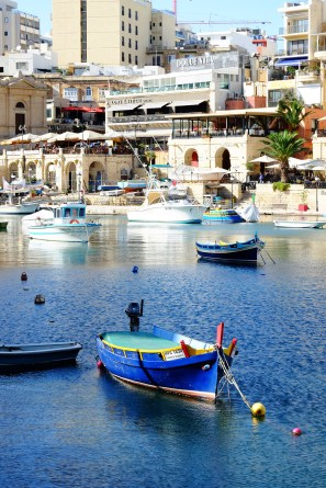 Traditional fishing boats and trendy al fresco cafes at Spinola Bay in St Julian's