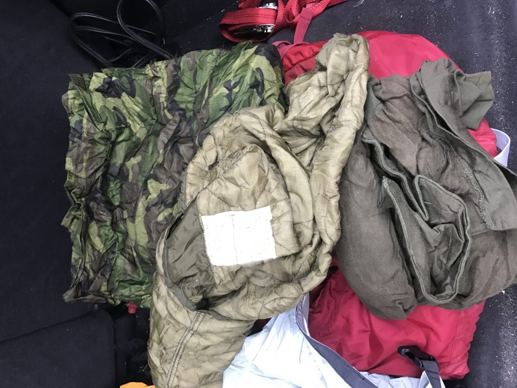 I also keep an Osprey Talon 44 pack ready for bugging out and stocked with climbing gear; the climbing gear is there because during the winters there have been numerous vehicles that spun off the road into the woods. At many junctions along the road the drop off is immense and would require someone to descend or climb out from to get help. Bugout bags have been covered as well, but mine contains some cold weather survival items that will assist in the event I am trapped in snow, or need to stay warm for hours or days. To assist in keeping warm, I have a signaling, shelter, and warmth generator such as a red-colored thermal tarp; a great item to have for these or other problems that could arise. A poncho is a must for backup shelters, and keeping the rain off, during flat tire changes. My poncho of choice is the Hazzard 4 poncho villa (https://www.hazard4.com/poncho-villa.html). The next items in the pack should be a water collector, a fire starter (magnesium is the best), a compass, and some layers of clothing to keep you dry and warm. My extra layers are in a water-proof compression sack that contains, a poncho liner, M-65 Field Jack liner, amilitary E.C.W.C.S., (Extended Climate Warfighter Clothing System) sleep shirt, and a wool balaclava.