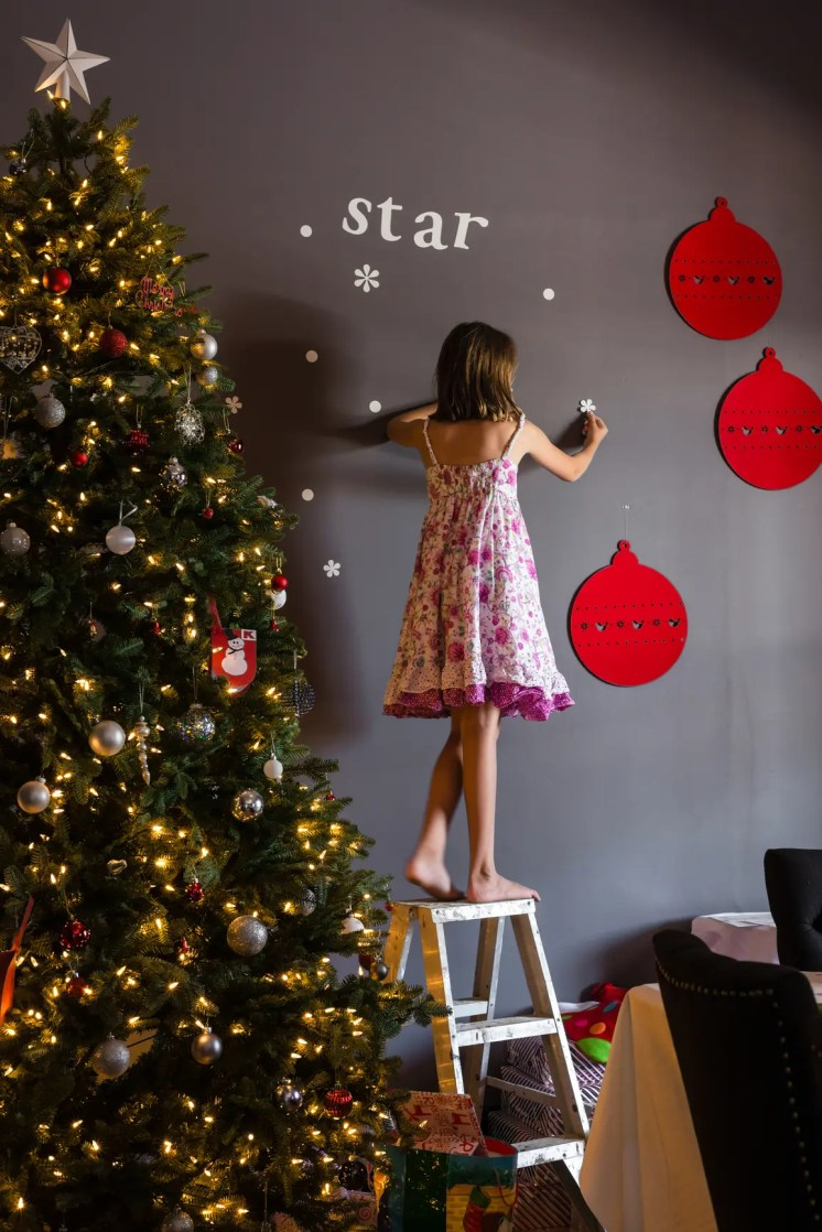 little girl placing decorations on the wall next to xmas tree