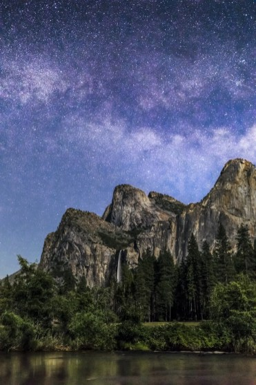 Bridal Veil Falls plunges between Cathedral Rocks and the Leaning Tower topped by the Milky Way on a moonlit night as seen from Valley View along the Merced River in the Yosemite Valley of California, USA.