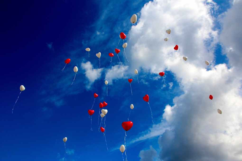 white and red plastic heart balloon on sky during daytime