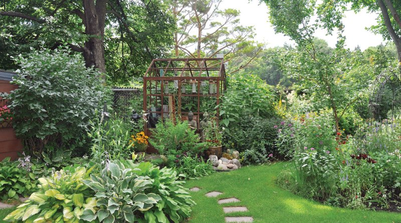 In the lush green beds of the backyard, the Victory Orangery greenhouse is barely visible.