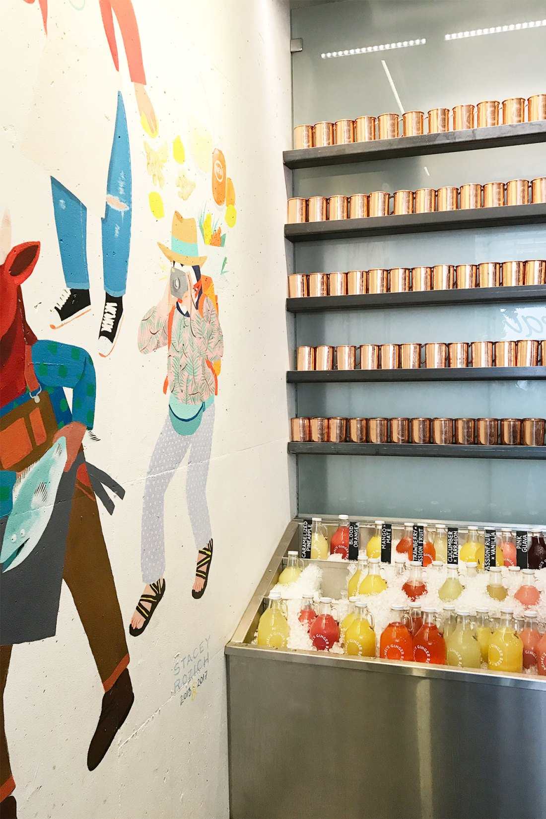 Colorful mural next to display of drink product