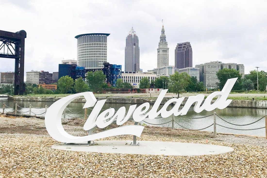 The word Cleveland in script font in front of downtown scene and a river