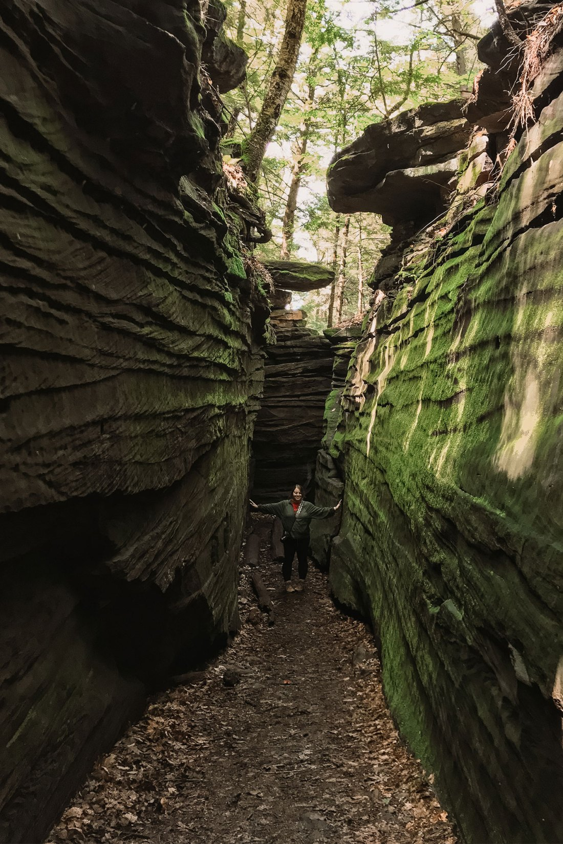 Woman standing between moss covered rock formations
