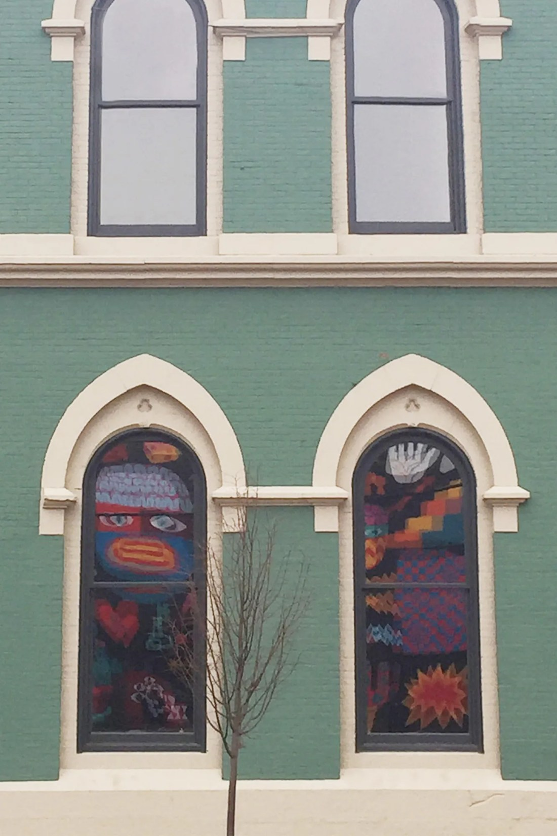 Building with mural reflecting in windows