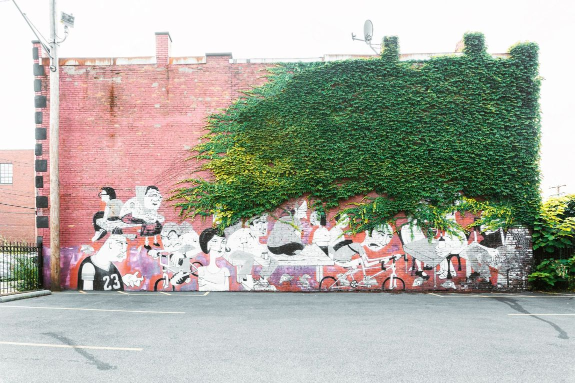 Mural of people on brick wall covered by vines
