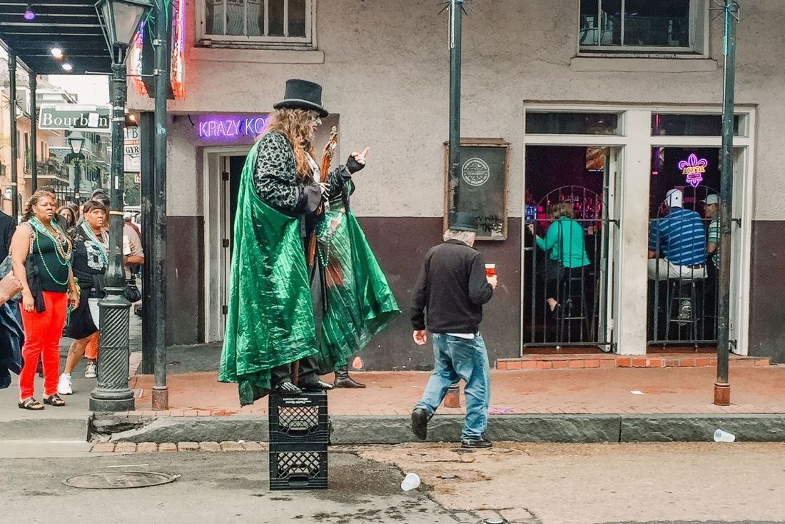 Man in green cape standing on crate on the street
