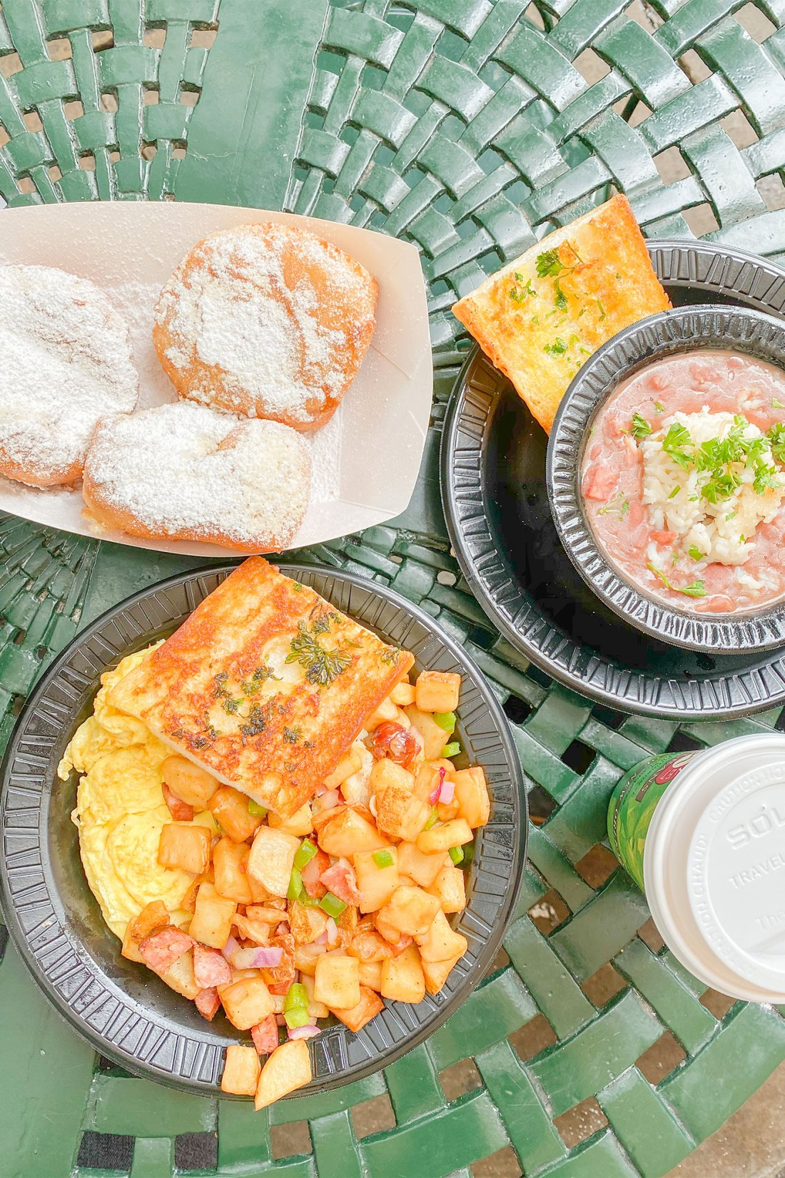 potatoes, eggs, toast, and beignets on table