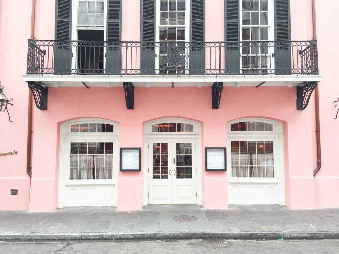 Pink building with white doors and wrought iron fence balcony in New Orleans