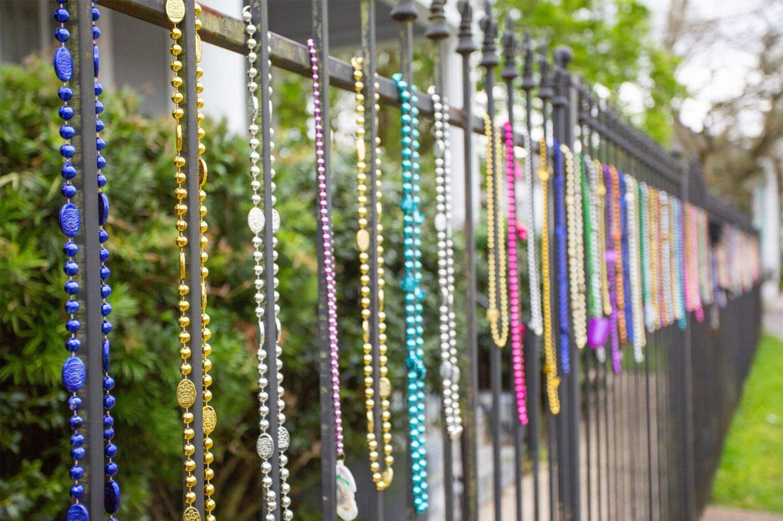 Wrought iron fence with colorful Mardi Gras beads draping in New Orleans