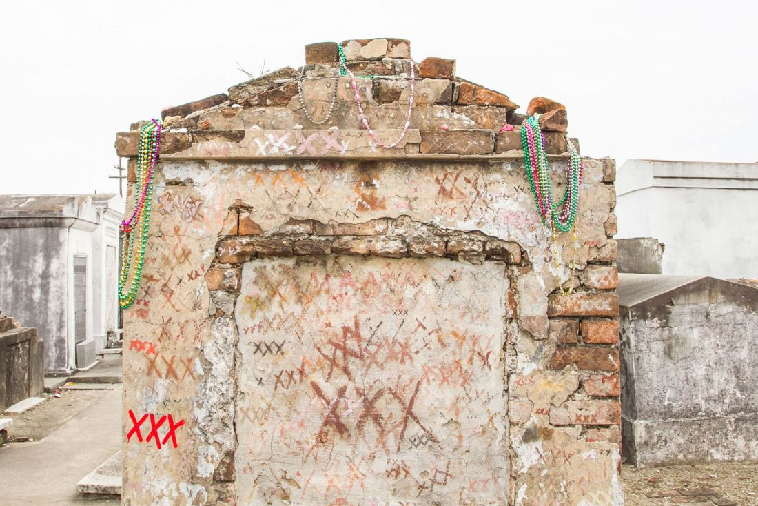 Tomb with colorful graffiti x's and Mardi Gras beads draped in New Orleans