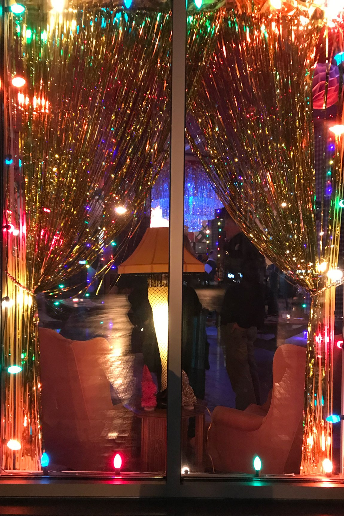 Tinsel and Christmas Lights in a window with the leg lamp
