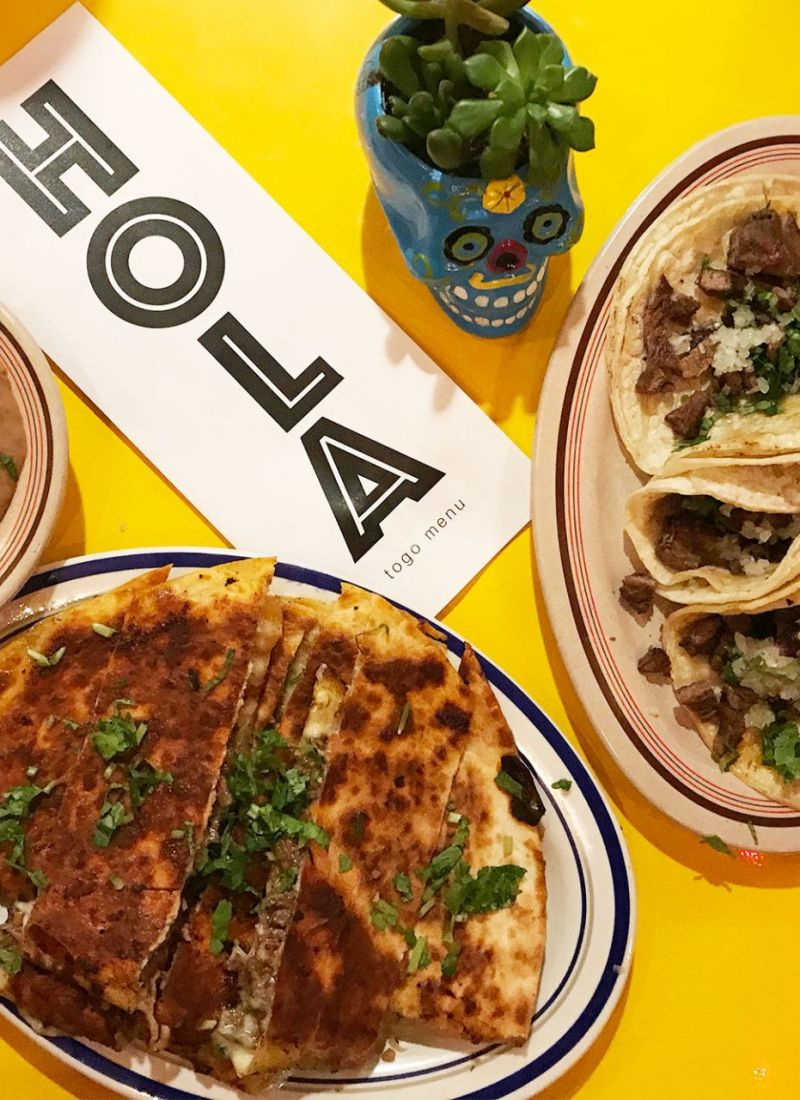 Mexican food spread on bright colorful table at Lakewood, Ohio's newest taco joint Hola Tacos.