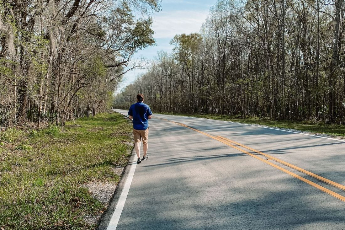Man walking on the side of a highway