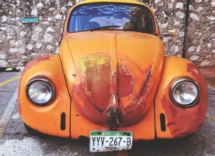 Close up of orange Volkswagen viewed from the front.