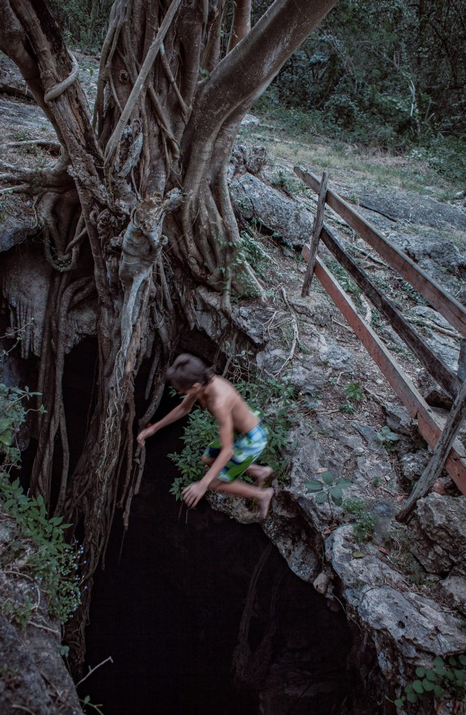 a boy jumps into a cenote from above