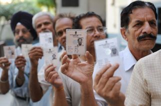 Indian voters hold up their voter ID cards as they stand in a queue to cast their vote at a polling station in Amritsar on May 13, 2009. during the final phase of polling for national elections.  India voters cast their final ballots in the country's marathon elections, with analysts predicting a shaky coalition government that will struggle to survive a full term.   AFP PHOTO /NARINDER NANU (Photo credit should read NARINDER NANU/AFP/Getty Images)
