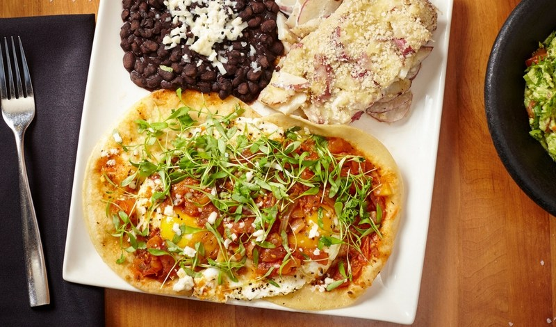 huevos rancheros traditional egg dish topped with ranchera sauce. served with potato confit and black beans
