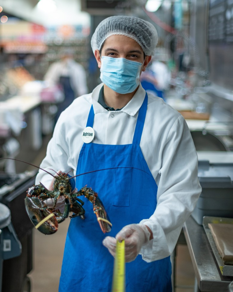 Grocery store employee holding a lobster