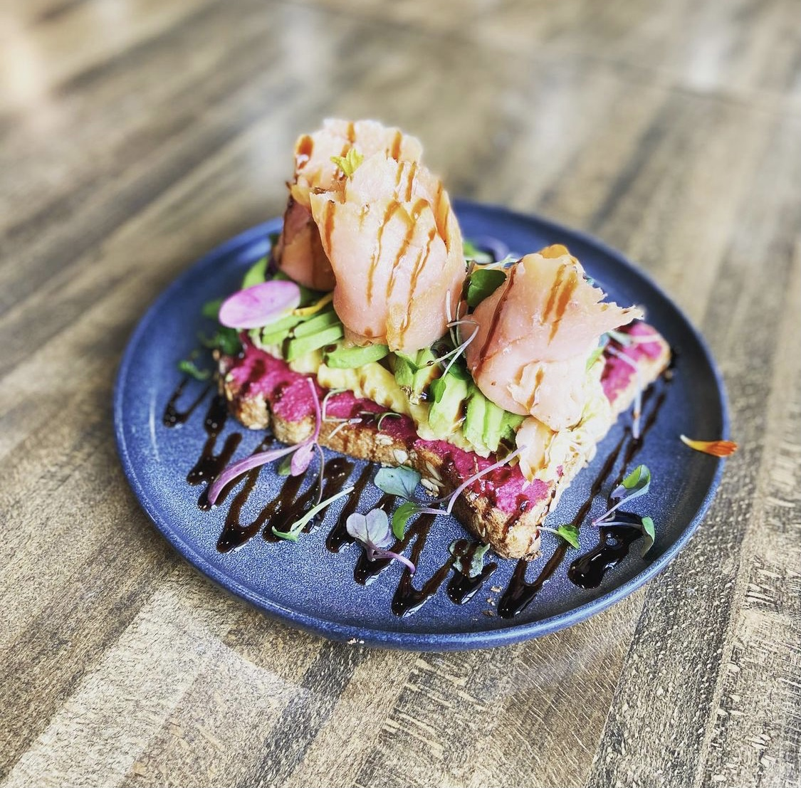 the sunrise toast from the nest, made with house-made beet hummus, scrambled egg, avocado, smoked salmon and a balsamic glaze. a favorite among healthy places to eat in frisco!   via @thenestcafetx on instagram