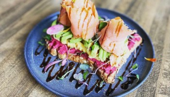 The sunrise toast from The Nest, made with house-made beet hummus, scrambled egg, avocado, smoked salmon and a balsamic glaze. A favorite among healthy places to eat in Frisco! | Via @thenestcafetx on Instagram