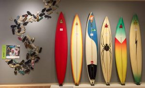 Barney Levy Jr.'s flip flop sandals, and Bob Pearson's surfboards archiving his history as a surf culture legend.