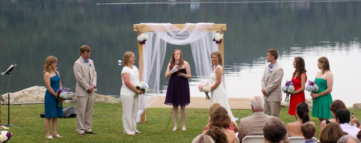Two brides at country wedding beside a lake