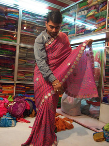 Salesman trying on a saree