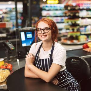 Pretty smiling cashier in eyeglasses and striped apron happily l
