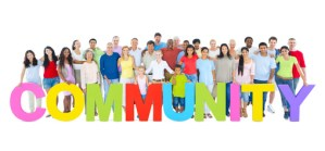 """Multi-ethnic group of people holding """"COMMUNITY"""" letters"""