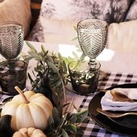 Una mesa con cuadros vichy y calabazas