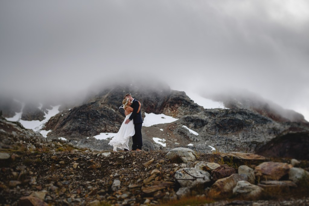 bride and groom on foggy mountain