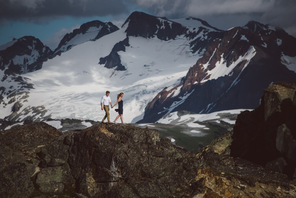 An engaged couple walking on the peak of Whistler Blackcomb