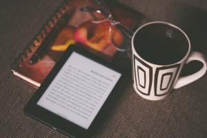 eReader, Notebook, Glasses and Cup of Coffee