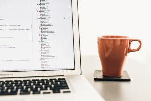 Laptop with Code and Cup of Coffee