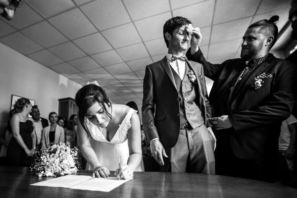 La marié signe tandis que le marié se fait éponger le front par son témoins