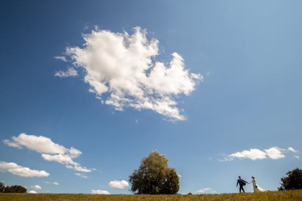 Les mariés marchent sur une crête sous un ciel bleu et ses nuages