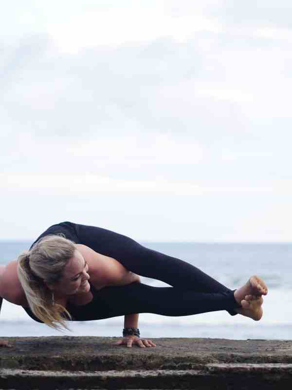 astavakrasana pose along the beach in Bali