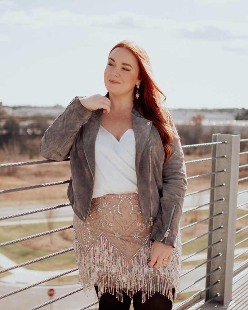 curvy blogger with red hair wearing suede moto jacket, plus size bodysuit and sequin skirt.