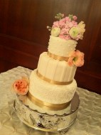 """""""Miranda"""" Ivory wedding cake with ivory accents and champagne ribbon border on silver cake stand"""