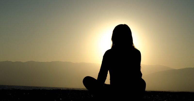 Silhouette of a lady sitting in the open and looking to the subnset